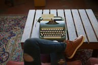 Cropped image of woman sitting on chair by typewriter at home - CAVF08637