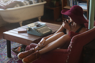 Happy woman drinking coffee while sitting by typewriter at home - CAVF08643