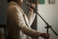 Midsection of woman holding microphone while standing at home - CAVF08646
