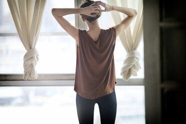 Rear view of woman tying hair bun while standing against window at home - CAVF08664