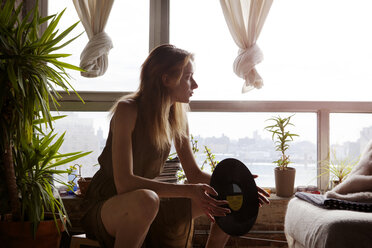Woman with record looking away while sitting by window at home - CAVF08667