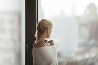 Side view of woman wrapped in towel standing by window at home - CAVF08685