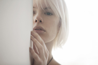 Portrait of woman hiding behind wall at home - CAVF08691