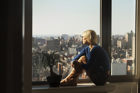 Side view of woman sitting on table by window at home - CAVF08694