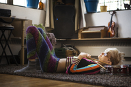 Woman lying on rug at home - CAVF08703