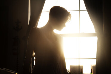 Woman standing against window at home - CAVF08715