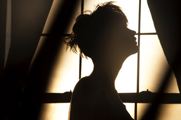 Silhouette woman standing against window at home - CAVF08718
