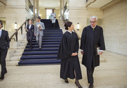Judges and lawyers walking through courthouse - CAIF16828