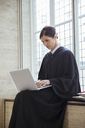 Judge sitting on bench using laptop in courthouse - CAIF16840