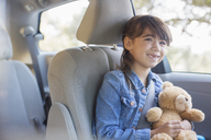 Happy girl with teddy bear in back seat of car - CAIF16909