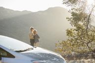 Senior couple looking at mountain view outside car - CAIF16933