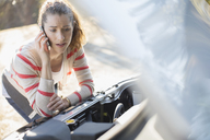Frustrated woman talking on cell phone and looking at car engine at roadside - CAIF16948