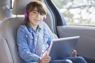 Portrait of smiling girl with headphones using digital tablet in back seat of car - CAIF16963