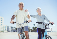 Senior couple with bicycles on beach - CAIF16969