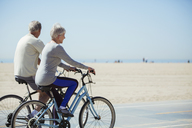 Senior couple riding bicycles on beach - CAIF16972