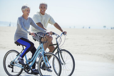 Senior couple riding bicycles on beach boardwalk - CAIF16984