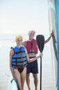 Portrait of senior couple with paddleboards on beach - CAIF16993