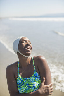 Woman in bathing suit and cap laughing on beach - CAIF17002
