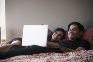 Smiling couple using laptop computer while lying on bed at home - CAVF08775