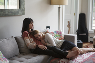Mother and daughter relaxing on sofa at home - CAVF08838