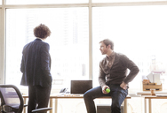 Businessman looking at coworker while sitting on table at office - CAVF08931