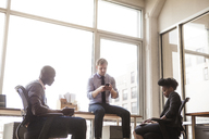 Business people using communication device while sitting at office - CAVF08934