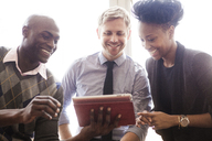 Happy business people looking at tablet in office - CAVF08937