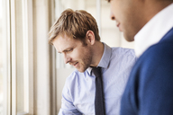 Close-up of businessman standing by coworker at office - CAVF08940