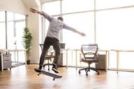 Rear view of man skateboarding at office - CAVF08946