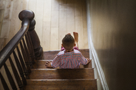 High angle view of boy sitting on stairs at home - CAVF08961
