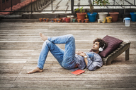 Man listening music while lying at floorboard - CAVF09033