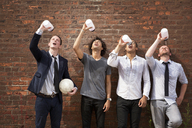 Friends drinking water while standing against brick wall - CAVF09054
