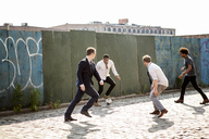 Men playing soccer by wall on street - CAVF09057