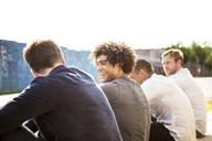 Happy friends sitting on footpath - CAVF09060