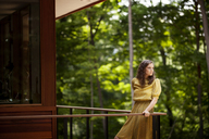 Young woman looking away while standing by railing in balcony - CAVF09117