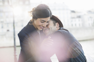 Couple hugging along Seine River, Paris, France - CAIF17039