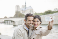 Couple taking self-portrait along Seine River near Notre Dame Cathedral, Paris, France - CAIF17069