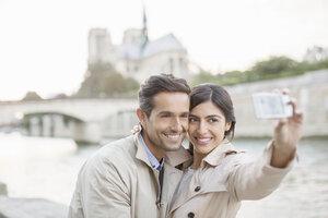 Couple taking self-portrait along Seine River near Notre Dame Cathedral, Paris, France - CAIF17069