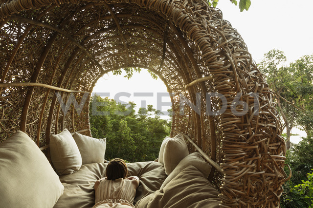 Woman laying in nest tree house - CAIF17087