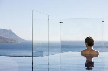Woman in infinity pool enjoying ocean view - CAIF17093