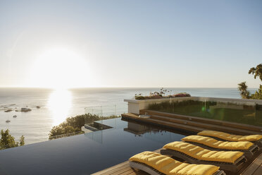 View of sunset over ocean from luxury patio - CAIF17096