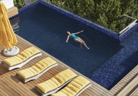 Woman floating in luxury swimming pool - CAIF17102