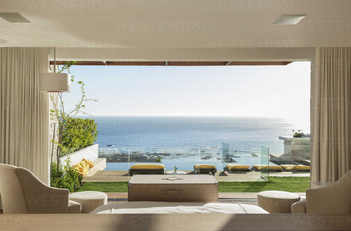Sunny bedroom and patio overlooking ocean - CAIF17105 - Astronaut Images/Westend61