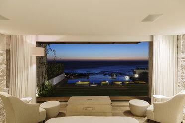 Modern bedroom overlooking ocean at night - CAIF17108