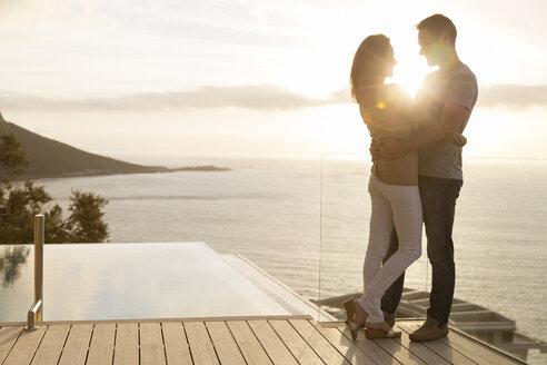 Couple on wooden deck overlooking ocean - CAIF17129