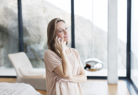 Woman talking on cell phone in modern living room - CAIF17138