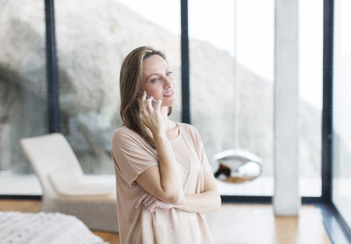 Woman talking on cell phone in modern living room - CAIF17138 - Astronaut Images/Westend61