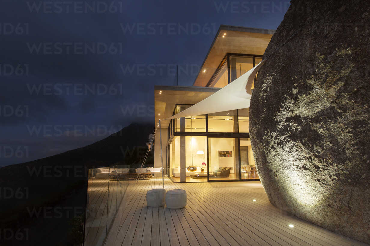 Illuminated modern house with rock feature and balcony - CAIF17147 - Astronaut Images/Westend61