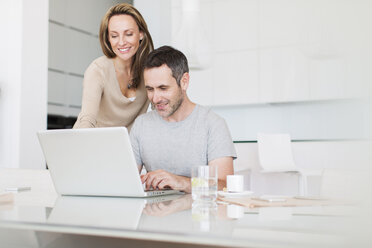 Couple using laptop at breakfast table - CAIF17153