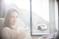 Woman having cup of coffee on sofa - CAIF17156